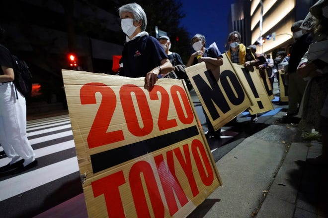 People opposed to the Tokyo 2020 Olympics, set to open in July, march around the Tokyo National Stadium during an anti-Olympics demonstration on Sunday May 9, 2021.
