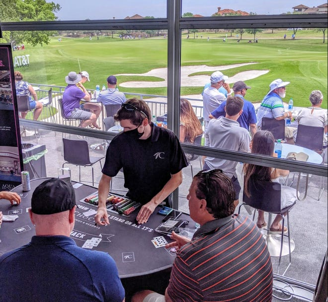 Patrons watch PGA Tour action on the 16th hole at TPC Craig Ranch while playing blackjack in the Choctaw Club.