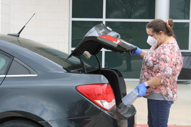 Karsen LaRue loads up a car with a customer's curbside pick-up order from the Pflugerville Public Library on March 27. The library will return to regular hours and discontinue quarantining returned items.