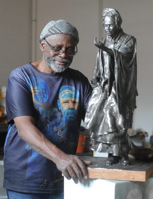 International sculptor Woodrow Nash with a small-scale model of the Sojourner Truth statue planned for downtown Akron.