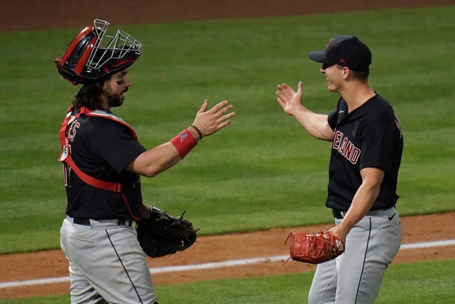 Cleveland relief pitcher James Karinchak, right, and catcher Austin Hedges celebrate their team's 3-2 win against the Los Angeles Angels in a baseball game, Wednesday, May 19, 2021, in Anaheim, Calif. (AP Photo/Jae C. Hong)