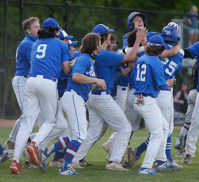 Revere's Sam Eberhardt, far right, is swarmed by teammates after he got to first on an errant throw that scored Andrew Froelich, far left, and lifted the Minutemen to a 5-4 win over Coventry in a Division II sectional final game Wednesday. [Karen Schiely/Beacon Journal]