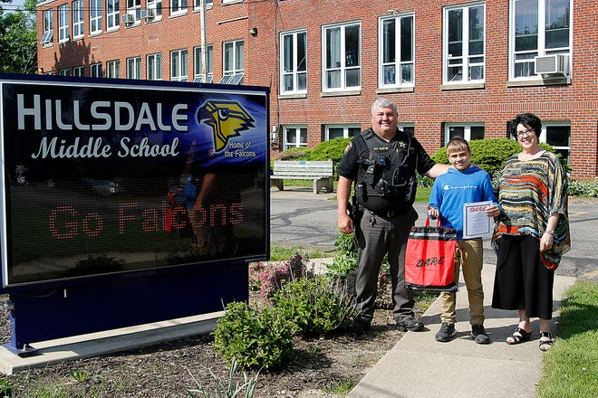 Ashland County Sheriff's Office Deputy Brian Martin poses with the county DARE essay winner, Hillsdale Middle School fifth-grader Reed Mager, and his teacher, Tiki Peterson, on Thursday, May 20
