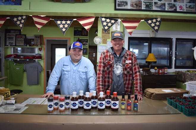 James Been, left, the owner of Knotwater Barbecue Company, has his products in several stores, including Slim's Country Market in Story City. The market, which is owned by Kurt Johnson, right, was the first establishment to put Beem's products on its shelves.