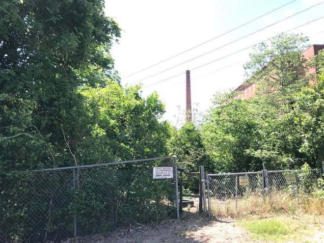 A fence lines inaccessible property that may become income-based housing in the shadow of King Mill.