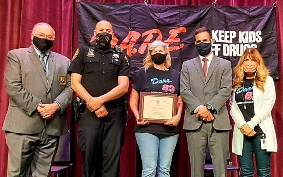 At the live-streamed DARE Graduation for Dundee 6th graders, retiring Elementary Principal Laurie Hopkins-Halbert was honored for her 28 years of service in Yates County schools. Seen here are: Sheriff Ron Spike, Deputy Charles Emerson - School Resource Officer, Principal Laurie Hopkins-Halbert, District Attorney Todd Casella, and DCS Superintendent Kelly Houck.