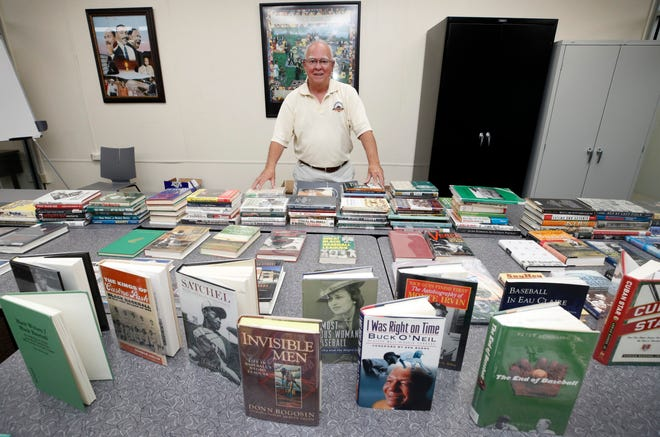 John Wakelin, a Lakeland retiree, poses with some of the Negro Leagues baseball-related books and ephemera he has collected over the decades. Wakelin is donating the collection to Bethune-Cookman University, which will house the items in its library.