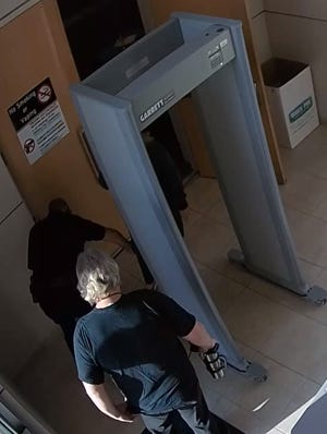 A Volusia County sheriff's deputy pats down Tammy Stuck after she set off the metal detector outside of the Deltona City Commission Chambers, while her husband, Jeff Stuck, stands nearby. The couple during a commission meeting Monday, May 17, publicly accused the deputy of inappropriate touching.