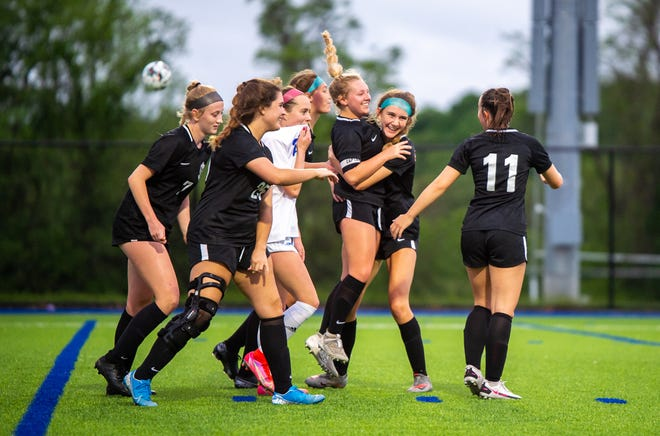 Lee's Summit North's Cassidy Calvin, third from right, is congratulated by teammates after scoring the final goal in the Class 4 District 13 championship Wednesday at Blue Springs South. The Broncos won 4-0 to claim their seventh straight district title.