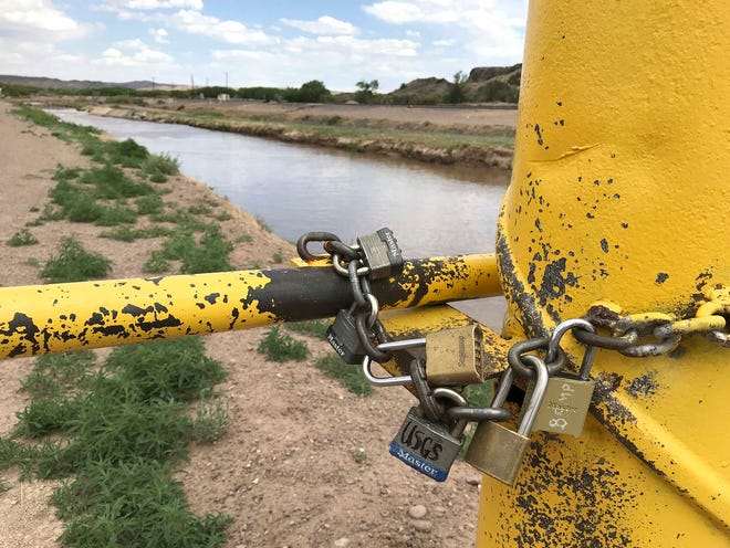 In this May 9 photo, a collection of locks are seen on a gate along an irrigation canal adjacent to the Rio Grande near San Acacia, N.M. More than two dozen farms farther south in the lower Rio Grande Valley have applied for a program that will pay them not to plant their fields for a year as water managers look for new ways to stretch resources in the arid state.