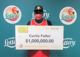 Curtis Fuller of Jacksonville poses with an oversized check after claiming a $1 million top prize from the 50X the Cash scratch-off game at Florida Lottery headquarters.