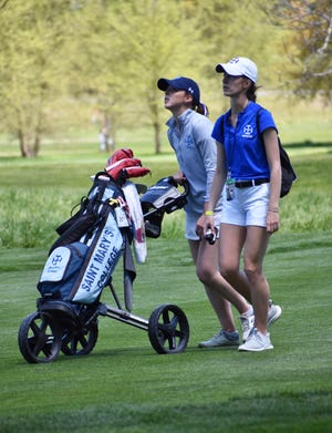 Saint Mary's senior Hunter Kehoe, left, and Jordan Koehler, the Belles' golf coach, analyze a shot in the final round of the 2021 NCAA Division III Women's Golf Championships on Friday, May 14, 2021 at Forest Akers Golf Course in Lansing, Michigan.