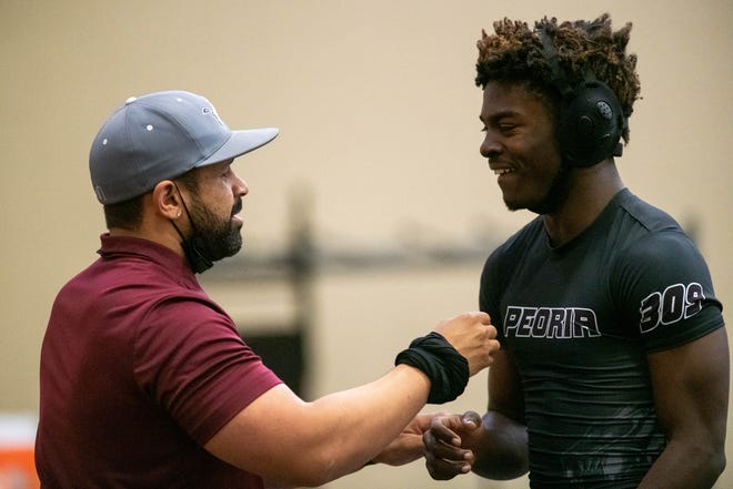 Peoria High wrestling coach Shaun McGinnes congratulates Nesha Robertson after Robertson pinned his opponent at Peoria High School on Wednesday. Robertson is one of many athletes who are competing in multiple sports this spring because of COVID-19 related delays.