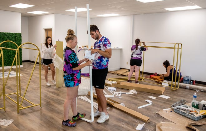 Sydney Jensen and her boyfriend, Daniel Saguar, foreground, assemble furniture while Natalie Collison, far left, Jordan Myers, far right, and Ashley King assemble racks as the Hello Poppy Boutique prepares for its grand reopening Saturday at its new location on Sheridan Road in Peoria.