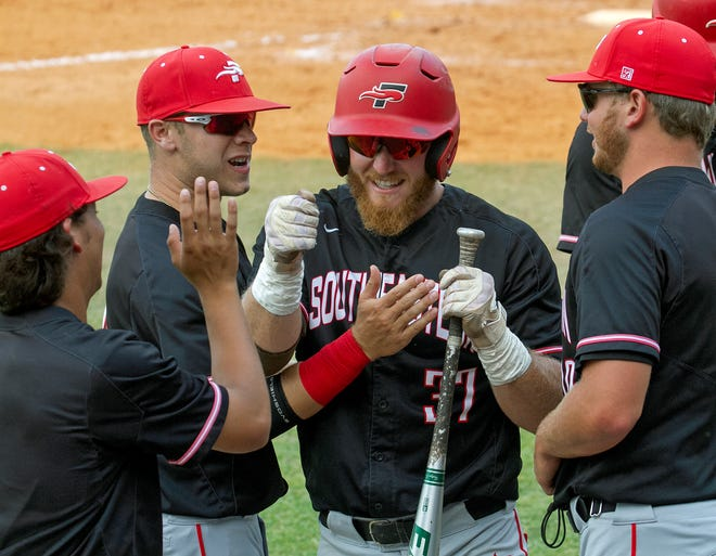 Southeastern University's Colton Onstott (37) is congratulated after scoring during the third inning against Middle Georgia State University at Chain O' Lakes Park in Winter Haven Wednesday night.