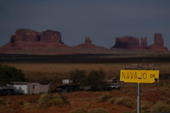 In this April 30, 2020, file photo, a sign marks Navajo Drive as Sentinel Mesa, homes and other structures in Oljato-Monument Valley, Utah on the Navajo Reservation, stand in the distance. Navajos clamored to enroll or fix their records as the tribe offered hardship assistance payments from last year's federal Coronavirus Aid, Relief and Economic Security Act. That boosted the number the tribe had in its vital statistics from about 310,000 to nearly 400,000 enrolled Navajos. The figure tops the Cherokee Nation's enrollment of 392,000. (AP Photo/Carolyn Kaster, File)