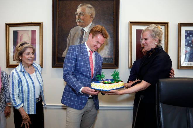 Landmarks Preservation Commissioner Sue Patterson (right) surprises commission chair Edward 'Ted' Cooney with a cake at his last commission meeting while Commissioner Jacqueline Albarran looks on in this February 2020 photo.