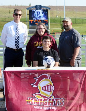 Petoskey senior Hunter Hicks (sitting) made things official to join the Calvin University men's soccer program. Hicks was joined at Northmen Stadium by (from left) PHS soccer coach Zach Jonker; mother, Samantha Hicks; and father, Jim Hicks.