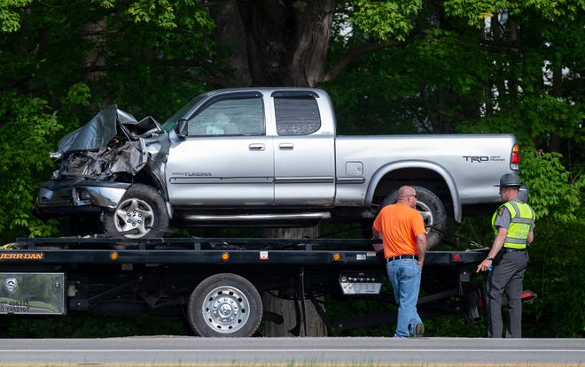 An Ohio State Highway Patrol officer talks to a tow truck driver after inspecting a Toyota Tundra following a crash on Route 88 in Ravenna Township on Thursday morning. The highway patrol says the Toyota crashed into the back of a minivan, pushing it into the rear of a stopped James A. Garfield school bus. The three men in the minivan suffered serious injuries when the vehicle caught fire. Four students on the bus suffered minor injuries.