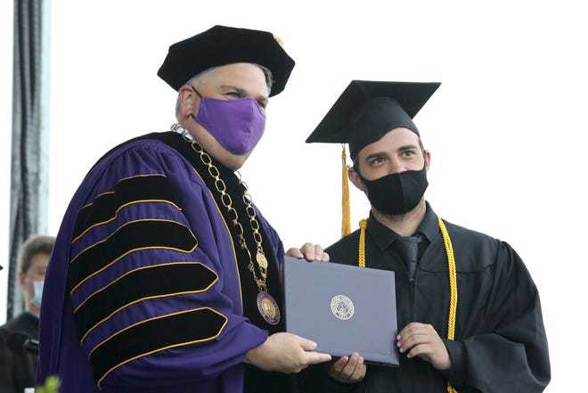 Rockford University President Eric Fulcomer and graduate Daniel Rosenstiel wear masks while posing for a photo Saturday, May 15, 2021, during the Rockford University graduation ceremony. The university will not require students to be vaccinated when returning to campus in the fall, but asks anyone not vaccinated to wear a mask.