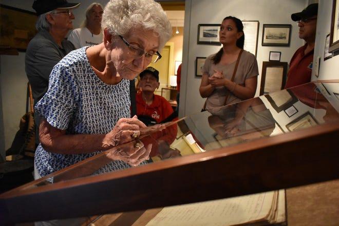 Julie Slavin, widow of Citizen Potawatomi Nation District 1 Legislator Roy Slavin, studies the census book of 1862 at St. Marys Pay Station Museum during Potawatomi Gathering in 2018.