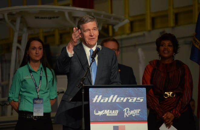 N.C. Governor Roy Cooper announces the acquisition of Hatteras Yachts by boat manufacturer White River Marine Group during an appearance at the Hatteras New Bern facility Thursday. White Water Group said it plans a $34 million investment with a target of adding 500 new jobs. [TODD WETHERINGTON / SUN JOURNAL STAFF]