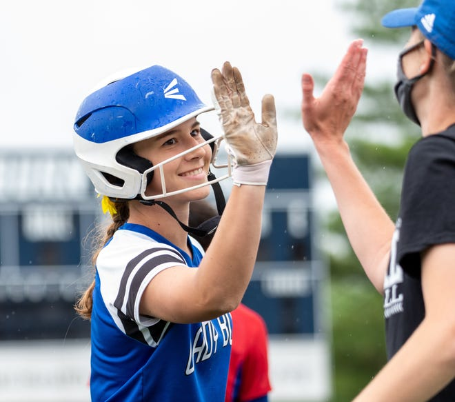 Washburn Rural's Kaci Bath gets a high five from head coach Tricia Vogel during the Junior Blues' Class 6A softball regional on Wednesday at Washburn's Gahnstrom Field. Rural dominated the regional, winning the title game 12-0 over Dodge City to advance to the Class 6A state tournament.