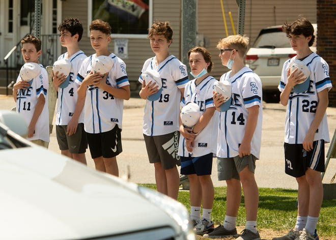 Teammates of Tyler Trudell, the 13-year-old who died in his sleep last week, show their support as his funeral procession passes through the center of Paxton on Thursday.