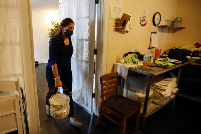 Maria Lanzas, catering director at Sweetwater Branch Inn, carries plates and helps clean up after an event Wednesday.