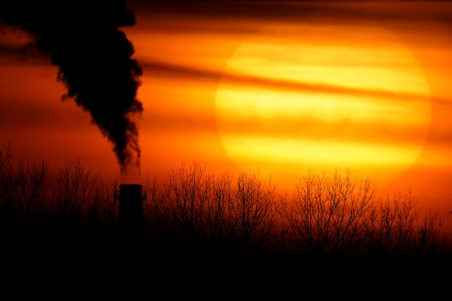 Emissions from a coal-fired power plant are silhouetted against the setting sun.