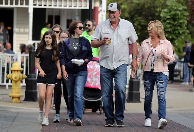 (From left) Haley Williams, 9, her mother, Beth Moorman-Williams, and Chris and Melanie Flaum, all of Grove City, cross Broadway during Heart of Grove City's first Food Truck Festival and Shop Hop of the season May 14. The city's Designated Outdoor Recreation Area was in effect for the event.
