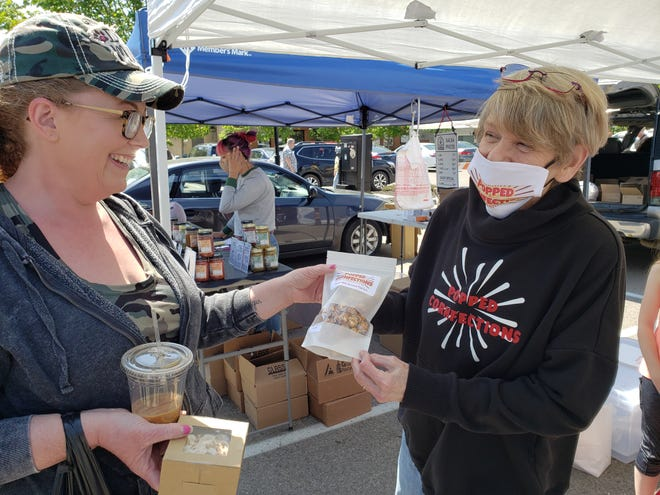 Popped Cornfections owner JoAnn Kostenbader (right) shows Grove City resident Stephanie Hansel a bag of her gourmet popcorn May 15 at the opening day of the 2021 Grove City Area Chamber of Commerce Farmers Market. There will be no mask requirements or social-distancing restrictions for this year's market, which will be held from 8 a.m. to noon each Saturday through the summer in the parking lot between the Broadway Station Apartments and the Grove City Library off Broadway.