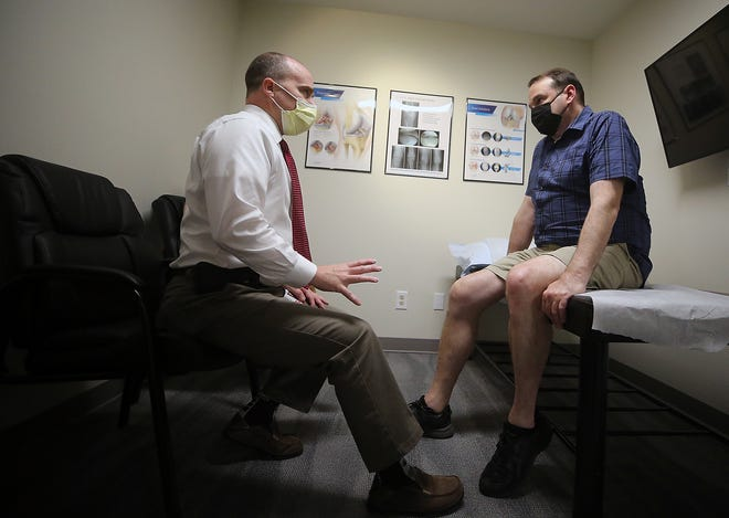 Dr. John West, left, talks with patient DJ Sweet during a post-op appointment at Liberty Knee Center in Poulsbo on Wednesday.