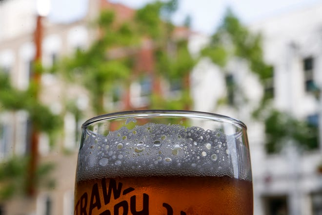 The head of a beer on tap slides down as bubbles pop in this photograph showing the downtown buildings across the street at Strawberry Alley Ale Works in Clarksville, Tenn., on Wednesday, May 19, 2021.
