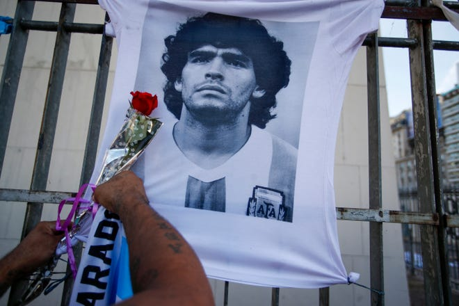 A man places a flower on a jersey with the face of late soccer star Diego Maradona during a march to demand answers regarding his death, in Buenos Aires, Argentina, Wednesday, March 10, 2021.