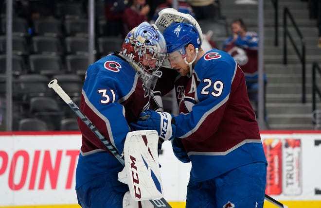 Colorado Avalanche goaltender Philipp Grubauer, left, is congratulated by center Nathan MacKinnon after Game 2 of the team's NHL hockey Stanley Cup first-round playoff series against the St. Louis Blues on Wednesday, May 19, 2021, in Denver.