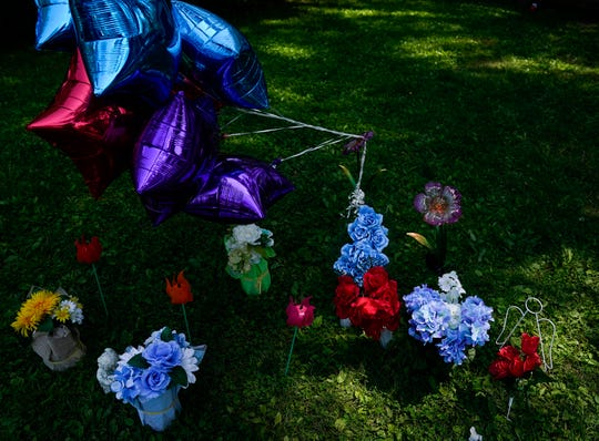 Family and friends of Dayshawn Bills placed balloons and flowers in the front yard of the home where the 12-year-old was shot and is in critical condition, Thursday, May 20, 2021, on the 3400 block of Leland Ave., in Indianapolis. Bills was hit by a bullet fired from the street while in his grandmother's home playing video games with family shortly after 3:30 a.m.