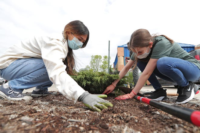 Elizabeth Pantoga-Montoto, 17, left, and Jaqueline Sandoval Ramirez, 15, plant shrubs as part of Teens Grow Greens in May at the Sixteenth Street Community Health Center, 4570 S. 27th St. Teens Grow Greens has a partnership with the health center that includes recruitment and referrals to each other's organization.