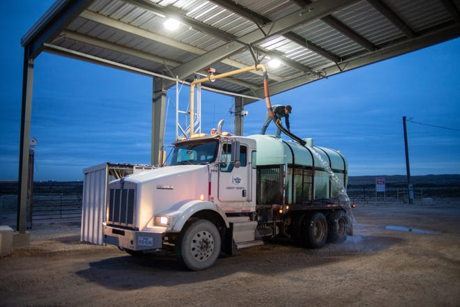 """A trucker """"top loads"""" water from a fresh water station near Black River, south of Carlsbad. Small trucks like these deliver fresh water for domestic use to oil workers' residences in camps throughout the region."""