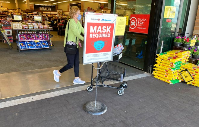 In this Wednesday, May 19, 2021, photograph, a shopper pushes her basket filled with purchases past a sign advising the need to wear face masks while in a Safeway grocery store in Aurora, Colo. Retail workers who are fully vaccinated are concerned as retailers loosen mask-wearing restrictions in their establishments. (AP Photo/David Zalubowski)