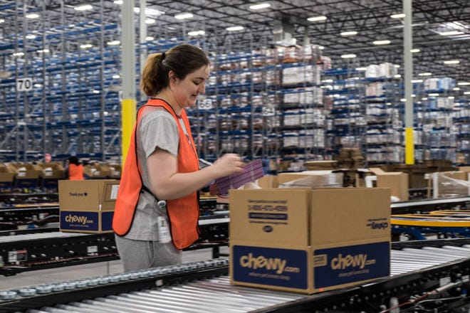 An employee working at Chewy's Sparks fulfillment center in 2018.