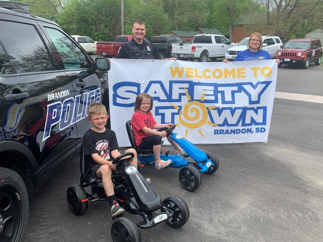 Trey Carda and Ashlynn David sit in their pedal carts as School Resource Officer Travis Carda and council member Vickie David hold the Safety Town banner for this year's event.