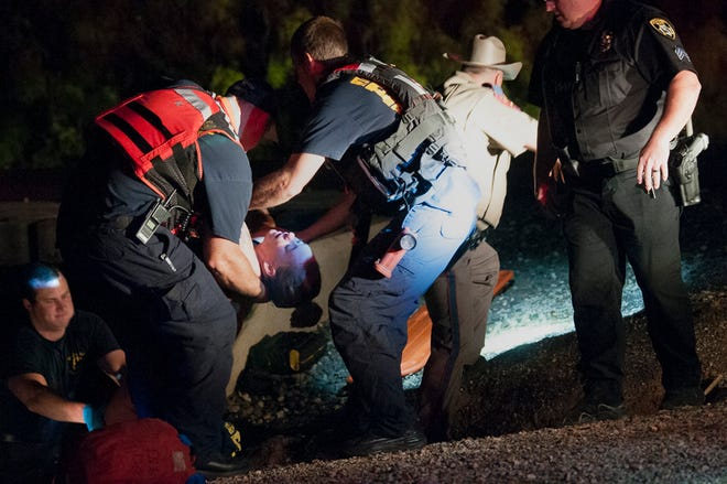 Wichita Falls Police and emergency medics worked to rescue a woman from the Wichita River Wednesday night.