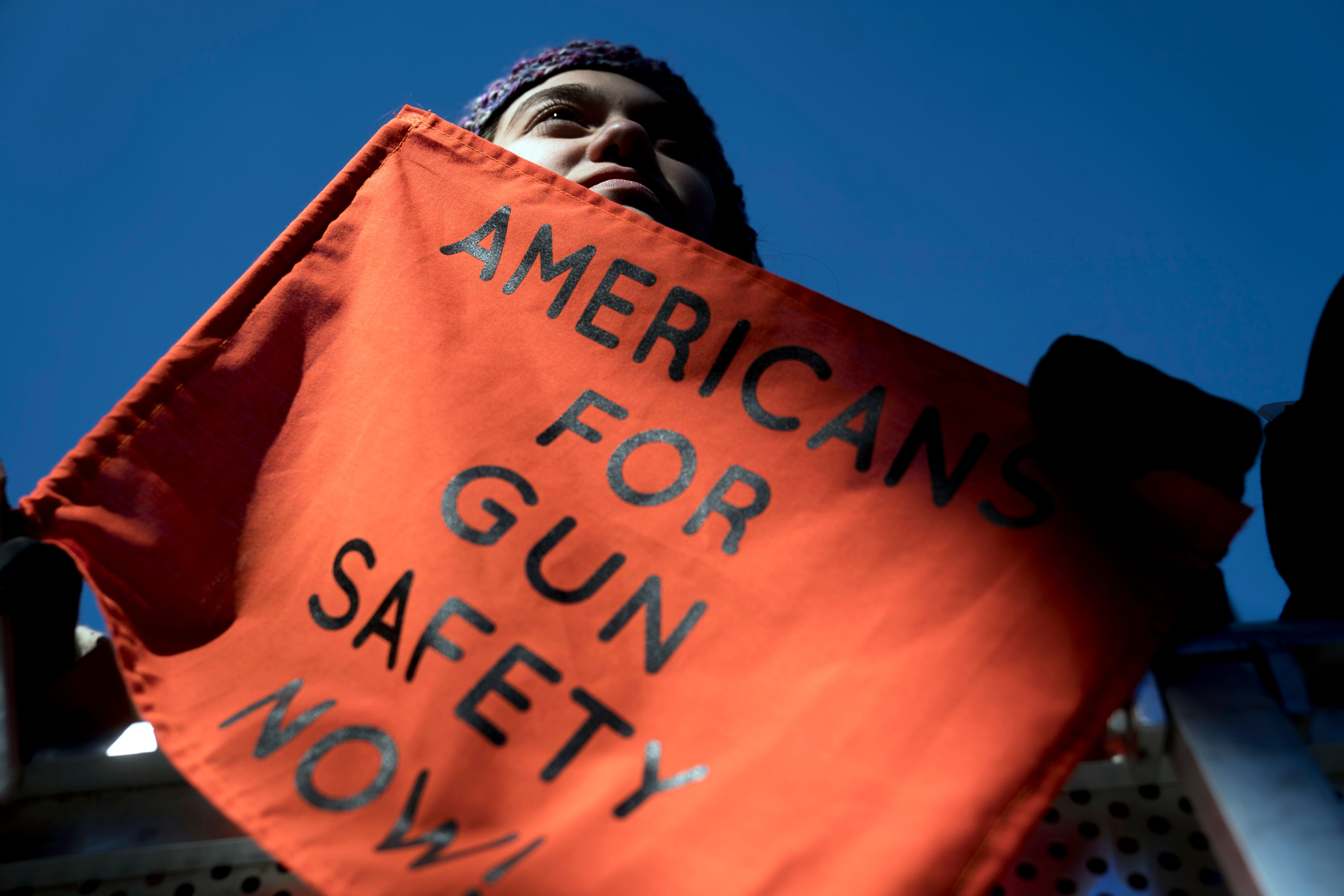"""In this March 24, 2018, file photo, Isabel White of Parkland, Fla., holds a sign that reads """"Americans for Gun Safety Now!"""" during the """"March for Our Lives"""" rally in support of gun control in Washington, that was spearheaded by teens from Marjory Stoneman Douglas High School after the 2018 mass shooting in Parkland, Fla. President Biden faces an uphill battle as he tries to push for more state laws that would allow authorities to temporarily disarm people who are considered a danger to themselves or others."""