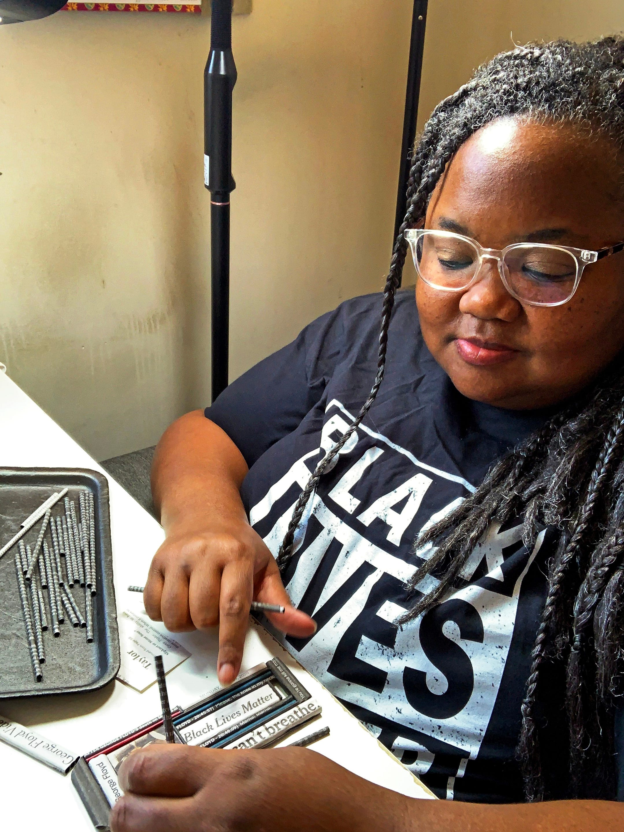 """Holly Anne Mitchell makes and sells jewelry fashioned from newspaper clippings. After George Floyd's murder, she made an elaborate """"I Can't Breathe"""" necklace featuring his likeness and headlines from the event. She is pictured here making that necklace."""