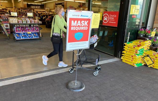 Un acheteur pousse son panier rempli d'achats devant un panneau indiquant la nécessité de porter des masques faciaux dans une épicerie Safeway à Aurora, au Colorado, le 19 mai 2021.