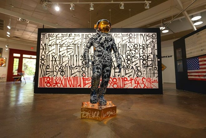 """At the West Chelsea Contemporary art show """"Icons & Vandals,"""" two pieces seem especially well-matched. In front is Brendan Murphy's sculpture, """"Boonji Spaceman."""" Behind it is Retna's painting, """"The Bottom Line Is Red."""""""