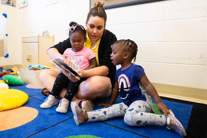 Mary Cadotte is shown in 2018 reading a book to Jaliyah Tharpe, left, and Sa'Miyah Brooks at the Mainspring Schools child care center in the Bouldin Creek neighborhood.