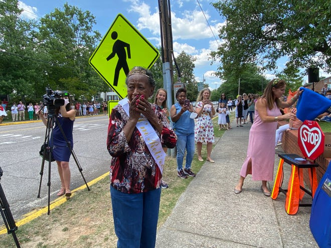 Margin Murray reacts as a plaque dedicated in her name is revealed at the corner of Monte Sano Avenue and Helen Street, where for 45 years she has worked as a crossing guard for St. Mary on the Hill Catholic School. Murray is retiring this year.