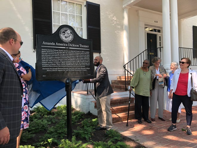 Corey Rogers (center), historian at the Lucy Craft Laney Museum of Black History, and Elyse Butler (second from left), marker manager for the Georgia Historical Society, unveil the marker at 448 Telfair St. in Augusta commemorating the former home of Black millionaire Amanda America Dickson Toomer. At far left is building owner John Hock, who funded and supervised the home's exterior renovations.